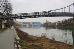 The pedestrian steel bridge Innsteg or Fünferlsteg in Passau, Germany. It connects the old town of Passau and the district Innstadt. The cityscape of Passau stock photo