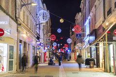 Pedestrian street illuminated by numerous Christmas decoration and shops on each side. Niort, France - December 05, 2017: pedestrian street illuminated by Royalty Free Stock Photo