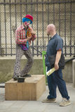 Pedestrian and street mime clown across from the Notre Dame Cathedral, Paris, France Stock Photo
