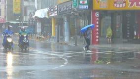 Pedestrian struggles to cross street in typhoon wind and rain. New Taipei City, Taiwan.  September 27, 2016: Pedestrians struggling to cross street during stock video