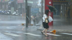 Pedestrian struggles to cross street in typhoon wind and rain stock video