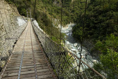 Pedestrian suspension bridge at a lush mountain above rocky river Royalty Free Stock Photo