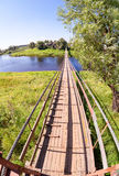 Pedestrian suspension bridge of steel and wood over the river Stock Images