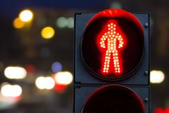 Pedestrian traffic lights red on a background of cars. And the city at night Stock Images
