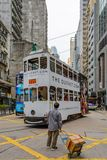 Pedestrian and tram at the crossroads in Hong Kong Street. China, Hong Kong - November 25, 2017: Pedestrian and tram at the crossroads in Hong Kong Street Royalty Free Stock Image