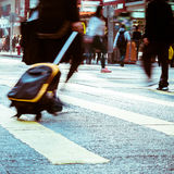 Pedestrian with travel bag walking at city street. Hong Kong. Blurred image of pedestrian with travel bag walking on crossroad at city street. Hong Kong. Art Royalty Free Stock Photos