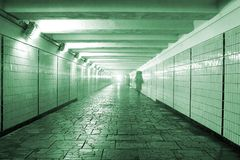 Pedestrian tunnel. With stone floor and tiled walls in Moscow near Kremlin with bright lamp at its remote edge and women silhouettes. Landscape orientation Stock Image
