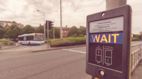 Pedestrian Wait Sign at Pelican crossing in both English and Welsh languages B. Shallow Depth of Field royalty free stock photography