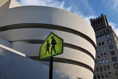 Pedestrian Walk Guggenheim Museum. MANHATTAN, NEW YORK - OCTOBER 11: A yellow  pedestrian street sign next to The Solomon R. Guggenheim Museum, a well-known Royalty Free Stock Photo