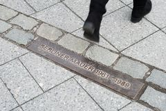 Pedestrian walking across commemorative plaque for Berlin Wall Stock Photography