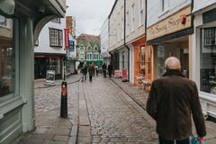 Pedestrian walking along cobblestoned street, with shops around it, and traditional architecture in the village of Canterbury, stock photography