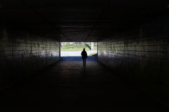 Pedestrian walking through dark tunnel Royalty Free Stock Photos