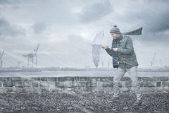 Pedestrian with an umbrella is facing strong wind and rain. A pedestrian is walking down a footpath on a dockside. He is opposing a strong wind and rain with an stock image