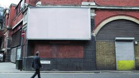 Pedestrian walking past a blank billboard