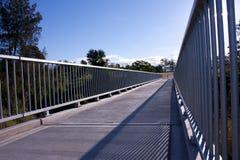 Pedestrian walkway bridge. A concrete and metal pedestrian walkway bridge with blue sky Stock Images