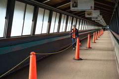 Pedestrian walkway for ferry. Bainbridge, WA, USA Feb. 11, 2017: Lone male figure walking through divided pedestrian walkway to board ferry boat to Seattle, WA Royalty Free Stock Images