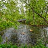 Pedestrian wooden bridge over stream Stock Photos