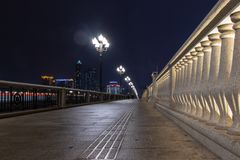Pedestrian zone on the stone bridge. Stone tiles, railings made of concrete marble baluster. Night background, illuminated lights along the road. Wet path stock image