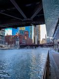 Pedestrians brave the plunging temps as steam rises from Chicago River. During January winter morning stock image