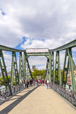 Pedestrians on the bridge Eiserner Steg in Frankfurt am Main, Germany. Stock Photo