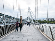 Pedestrians cross Jubilee Bridge over Thames River, London. London, August 20, 2015: Pedestrians cross Jubilee Bridge over the Thames River Stock Image