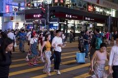 Pedestrians cross Nathan Road at Tsim Sha Tsui in Kowloon. stock photo