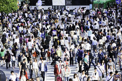 Pedestrians crossing the busiest crosswalk in the world in the Shibuya district in Tokyo, Japan Royalty Free Stock Photo
