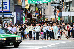 Pedestrians crossing the busiest crosswalk in the world in the Shibuya district in Tokyo, Japan Royalty Free Stock Image