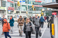 Pedestrians crossing a busy intersection. TORONTO, ON, CANADA - OCTOBER 30: Pedestrians crossing a busy intersection near Dundas Square on Young Street, in Royalty Free Stock Images