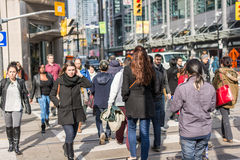 Pedestrians crossing a busy intersection. TORONTO, ON, CANADA - OCTOBER 30: Pedestrians crossing a busy intersection near Dundas Square on Young Street, in Stock Photos