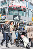 Pedestrians crossing a busy intersection. TORONTO, ON, CANADA - OCTOBER 30: Pedestrians crossing a busy intersection near Dundas Square on Young Street, in Stock Image