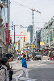 Pedestrians crossing a busy intersection. TORONTO, ON, CANADA - OCTOBER 30: Pedestrians crossing a busy intersection near Dundas Square on Young Street, in Stock Images
