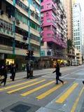 Pedestrians crossing Hong Kong Island street at crosswalk; skyscrapers Royalty Free Stock Photos