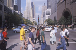 Pedestrians crossing Michigan Avenue, downtown Chicago, IL Stock Image