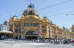 Pedestrians Crossing Road at Flinders Street Station, Melbourne, Australia. A large number of pedestrians heading to and from historic Flinders Street Station Stock Image