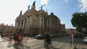 Pedestrians crossing road near beautiful historical building on sunny day, Lviv. Stock footage stock video footage