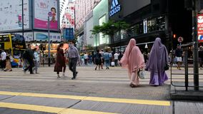 Pedestrians crossing the street in shopping District of Hong Kong stock video