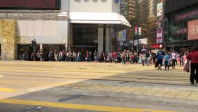 Pedestrians crossing the street in shopping District of Hong Kong stock footage
