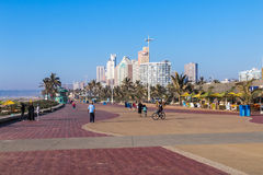 Pedestrians and Cyclists on Paved Beachfront Promenade stock photo