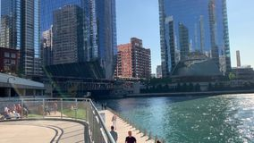 Pedestrians enjoy the summer vibes along the Chicago River riverwalk/walkway. On a bright afternoon stock footage