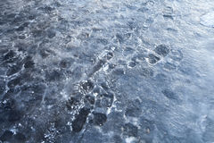 Street sleet background with frozen footprints. Pedestrians footprints in road blue ice. Street sleet background Royalty Free Stock Images