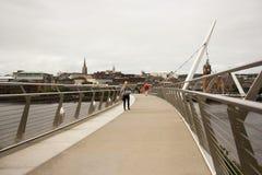 Pedestrians krzyżuje ikonowego pokoju most nad rzecznym foyle w Londonderry mieście w Północnym - Ireland Zdjęcie Royalty Free