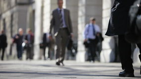 Pedestrians on a London pavement. Real-time video footage of anonymous pedestrians and office workers walking along a London pavement stock footage