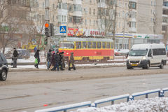 Pedestrians pass snow-covered road in the green light. Volgograd, Russia - January 22, 2016: pedestrians cross the snow-covered winter road on a pedestrian Stock Photos