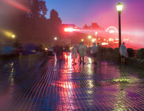 Pedestrians on a Rainy, Colorful Walkway Stock Photo