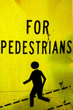 For pedestrians sign. Yellow sign with black text for pedestrians with walking figure graphic Stock Image