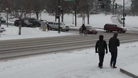 Pedestrians in a snowstorm stock video footage