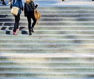 Pedestrians in stairs. Sunlit young female pedestrians walling up the stairs Royalty Free Stock Photo