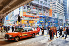 Pedestrians, taxi and double-decker trams on the central streets. Hong Kong is popular tourist destination of Asia and leading financial centre of the world Royalty Free Stock Photo