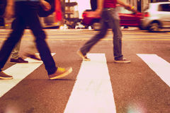 Pedestrians and traffic crossing the street. Anonymous people walking down the pedestrian lane. Everyday commuters. blurred stock photo